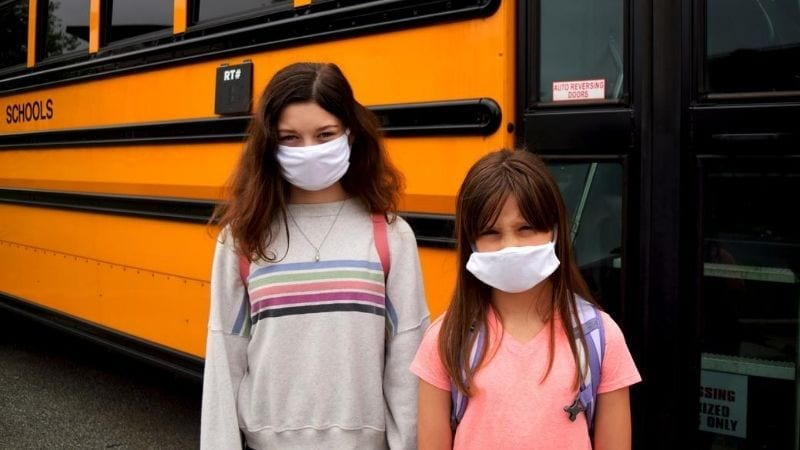 Two young girls standing next to the school bus while wearing white masks.
