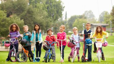 school children lined up in a row on their bikes and scooters