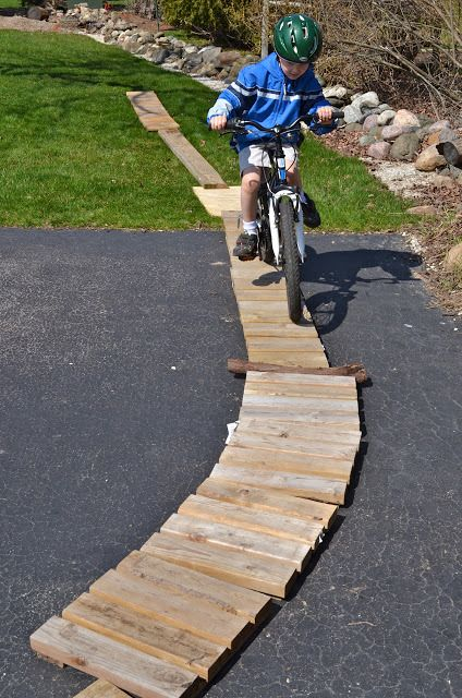 Child on bicycle riding on wood path