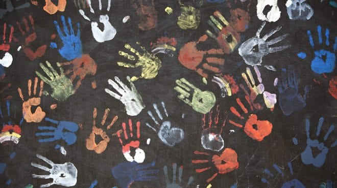 Colored hand prints on black paper.