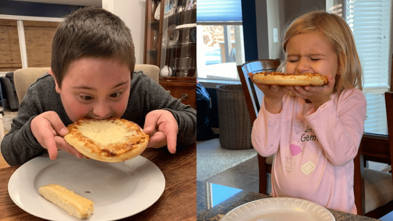 young boy and girl sitting at a table biting into pizza during pizza school funderaisers