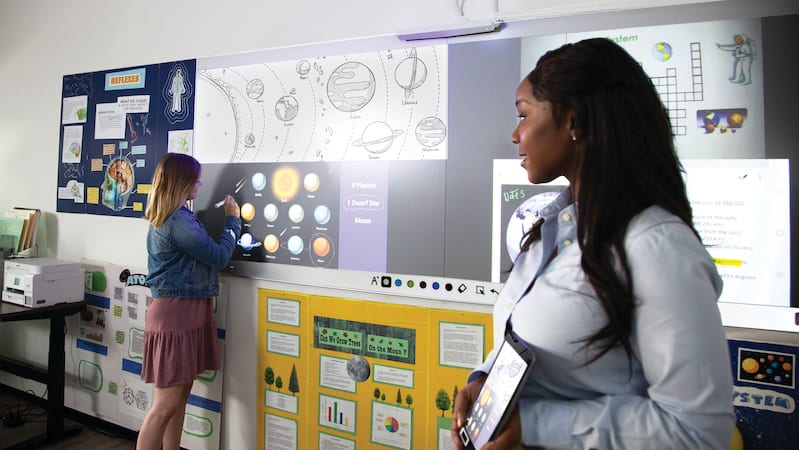 A whiteboard filled of posters of planets and the teacher holding up a tablet with planets.