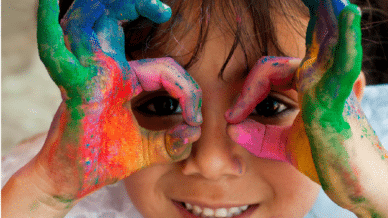 Preschool girl with hands covered in colorful paint - Early Childhood Resources