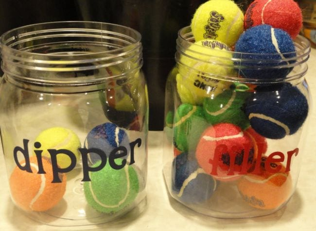 Two plastic jars labeled dipper and filler, with some colorful tennis balls in each