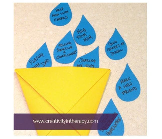 Small origami paper bucket with paper raindrops with bucket filler activities written on them