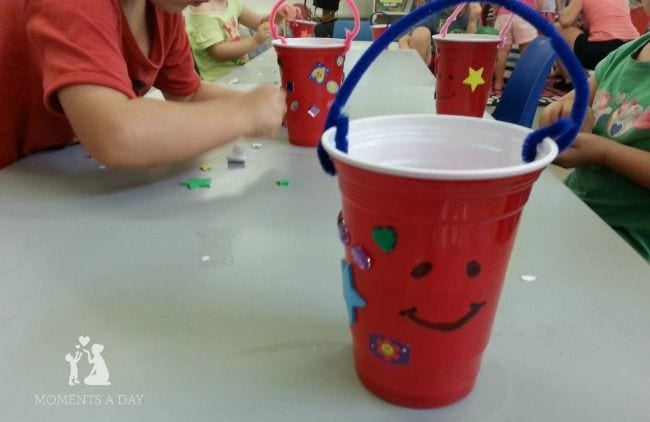Students decorating red plastic Solo cups with stickers and a pipe cleaner handle (Bucket Filler Activities)