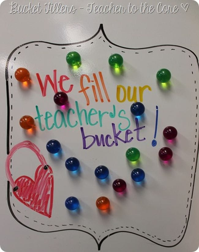 Colored magnets on a whiteboard with text reading We fill our teacher's bucket!