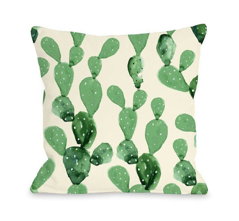 Beige throw pillow decorated with various green cacti