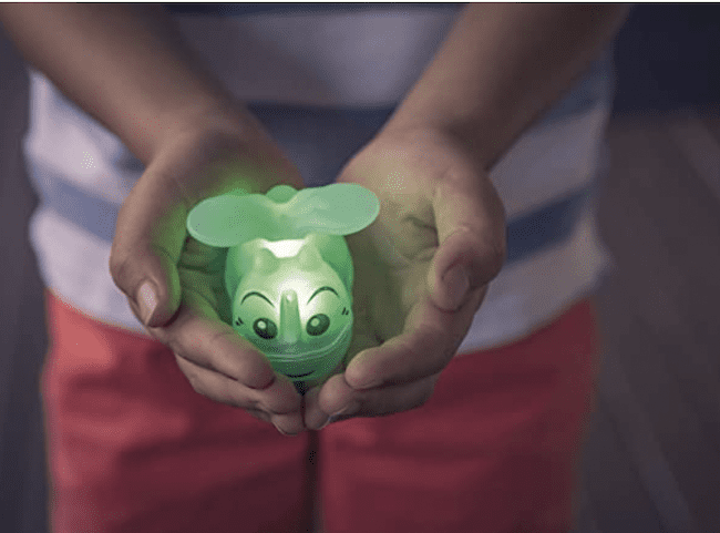 A child holding a glow in the dark firefly toy