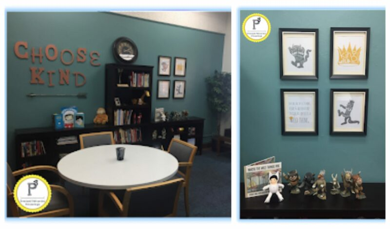 a principal's work space with a bright teal wall, table and chairs and a wall of bookcases. Also, four prints , action figures and the book Where the Wild Things Are