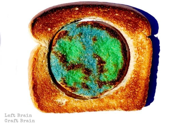 Piece of toast with center section cut out and milk painted to resemble Earth (Climate Change Activities)