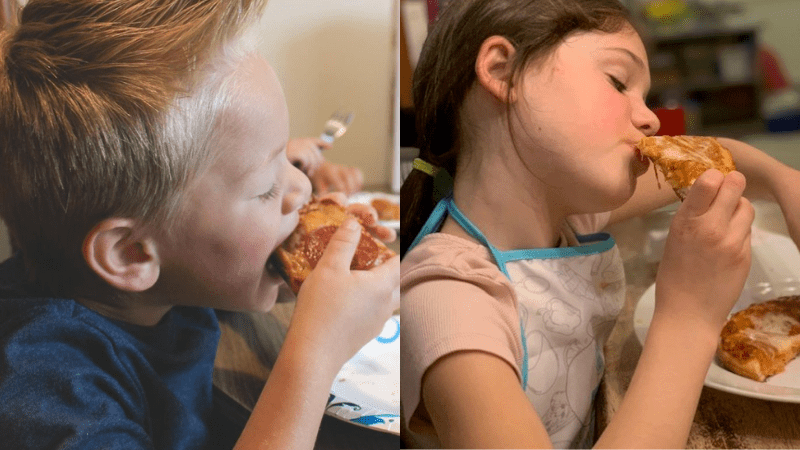 Close up of young boy and girl sitting at a table biting into pizza during pizza school funderaisers