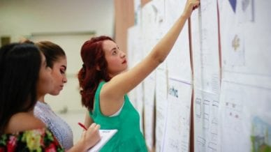 A young adult woman pointing at a poster hanging up while two other woman are taking notes.