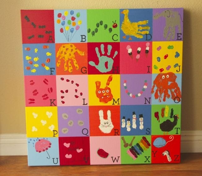 Canvas divided into squares with image representing a letter of the alphabet made with handprints or fingerprints in each (Collaborative Art Projects)