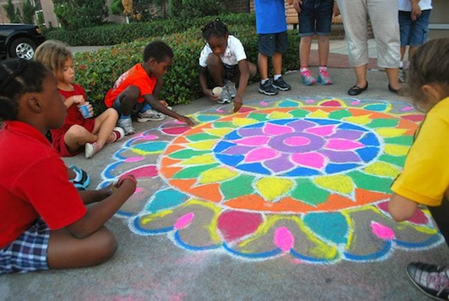 Students collaborating on a rangoli design made with chalk and sand