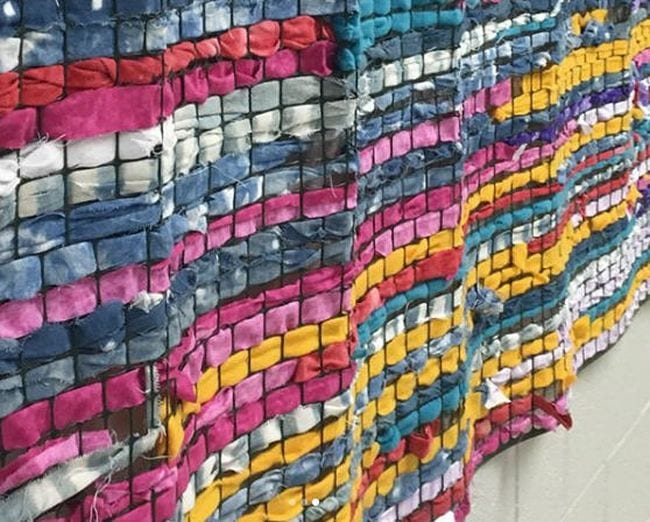 Fabric strips woven through chicken wire mounted on a wall in a wavy texture
