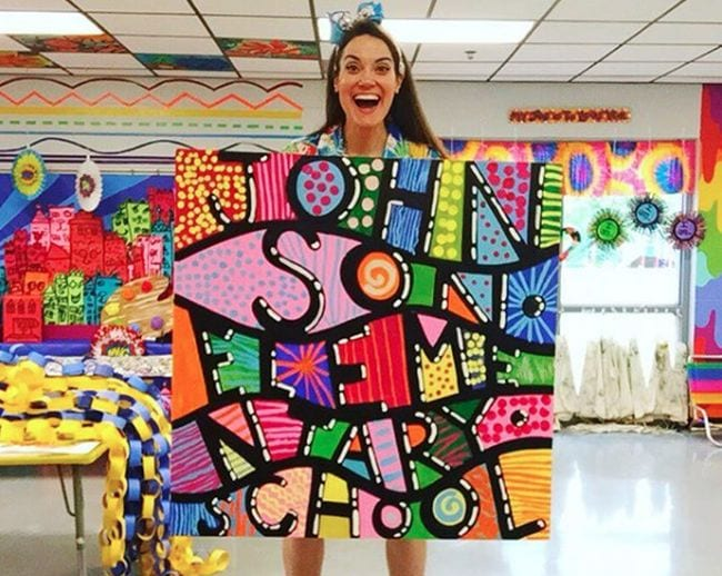 Woman holding a colorful mural poster lettered with Johnson Elementary School with patterns between the letters
