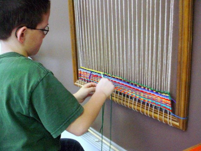 Child weaving yarn on a large loom mounted on a wall (Collaborative Art Projects)