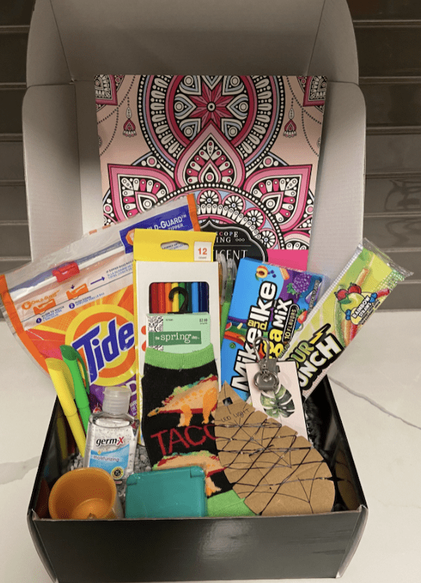 """A """"College Survival Kit"""" that has hand sanitizer, a stain stick, candy and other gifts for graduating seniors."""