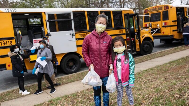 Asian American woman and daughter standing in front of school bus free meals for kids