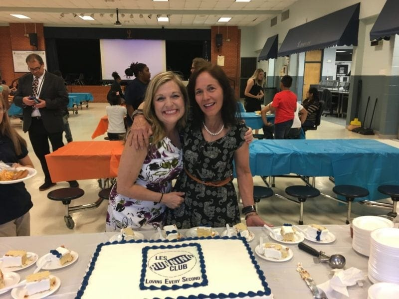Two teachers cutting a cake who advocate for student physical activity