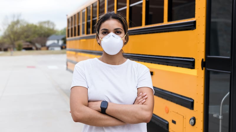A female school bus driver, wearing an N95 mask, stands next to a school bus. She is standing with her arms crosses and is looking at the camera.