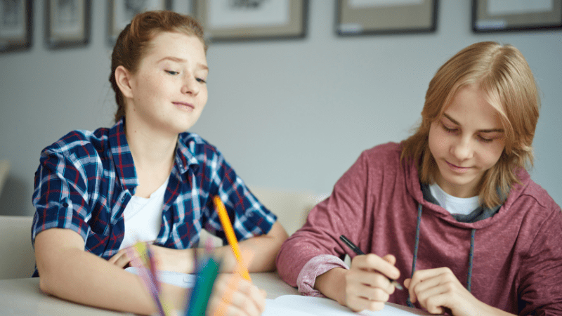 Female and male teens drawing on paper on a desk