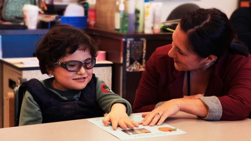 A young boy with glasses looking at a piece of paper with the teacher.