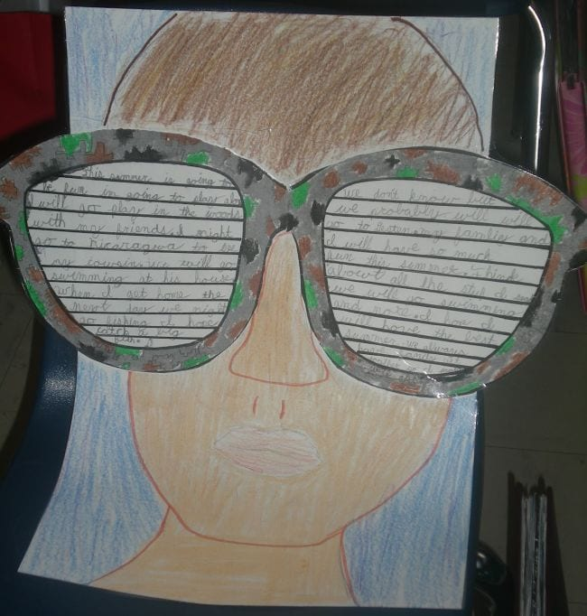 Crayon drawing of student wearing sunglasses, with written end of year assignment on the sunglasses