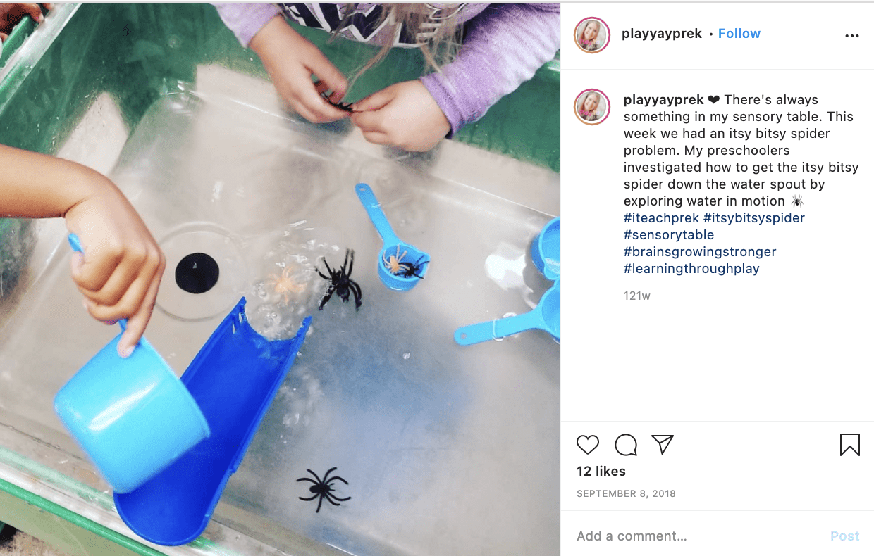 A picture of students playing with a water table that has fake spiders, a plastic spout, and measuring cups in it.