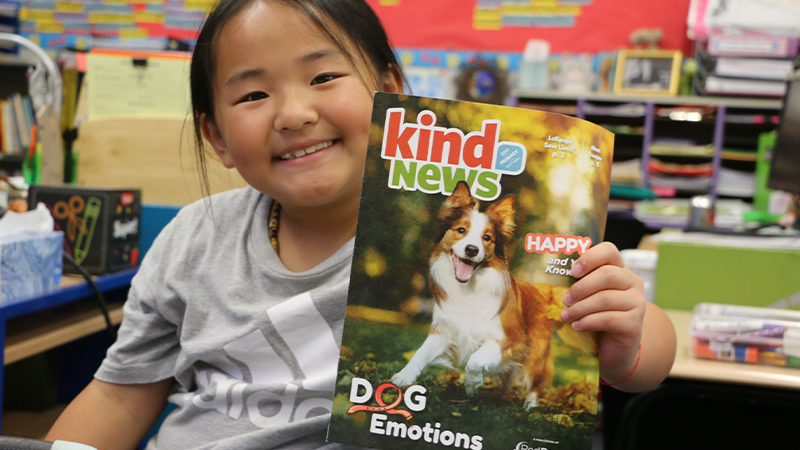 A young girl in her classroom holding up a dog magazine from kind news.