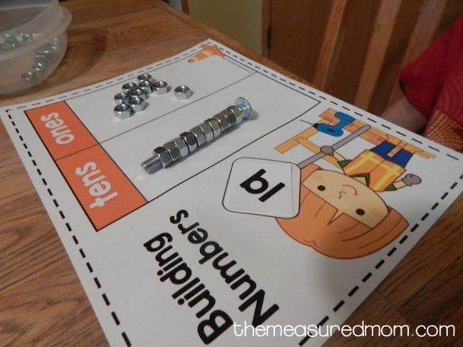 Building Numbers worksheet with picture of child in construction gear and nuts and bolts used to represent tens and ones