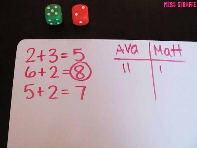 Pair of dice with a whiteboard with addition problems written on it (First Grade Math)