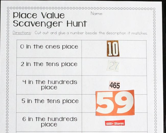 Worksheet labeled Place Value Scavenger Hunt with clues like 0 in the tens place, with numbers cut from magazines glued in place