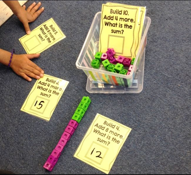 "Math cubes with printed cards saying ""Build 4. Add 8 more. What is the sum?"""