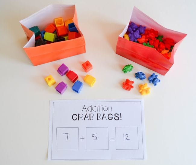 Colorful paper bags filled with math cubes and plastic bears, with a worksheet called Addition Grab Bags (First Grade Math Games)