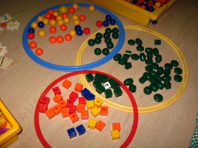 Large plastic hoops lying on the floor with math cubes, balls, and plastic beads sorted in them (First Grade Math Games)