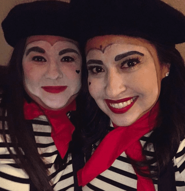 Two women wearing mime face paint, striped shirts, red scarves, and berets