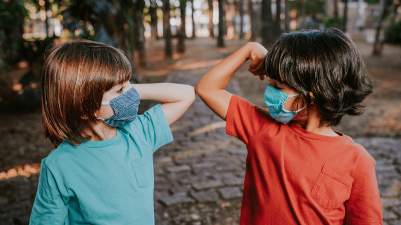 Two young boys touching elbows in the woods with their face masks on.