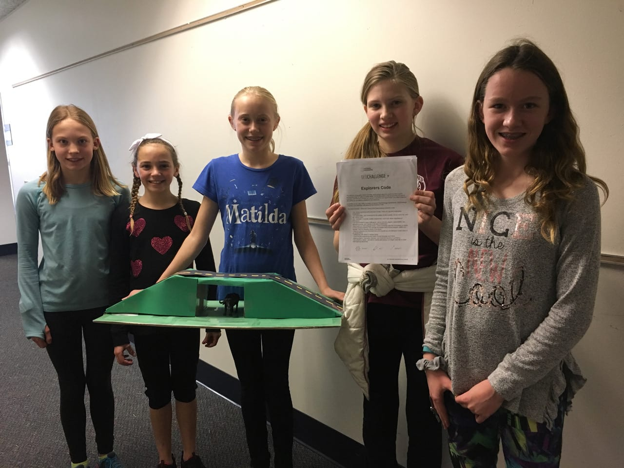 five students with their GeoChallenge STEAM project about wildebeests