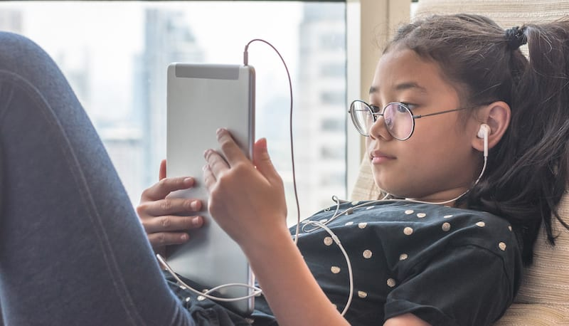 A child listening with earphones in connected to her tablet