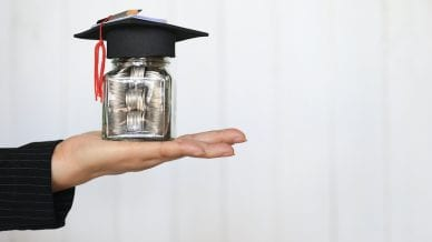Woman hand holding coins money in glass bottle with graduates hat on white background.