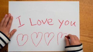 "A child writing on printer paper with the words, ""I Love You"" in red crayons with hearts underneath"