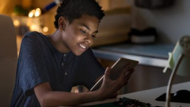 A young African American boy smiling at his tablet in the dark.