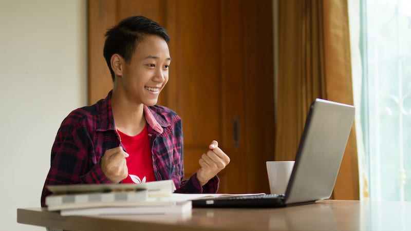Happy teenage boy feeling excited to see a good news in email from laptop at home.