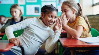 Shot of two young girls whispering to each other in a classroom