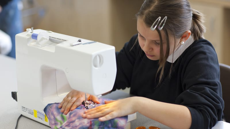 A female high school student using sewing machine in textiles class.