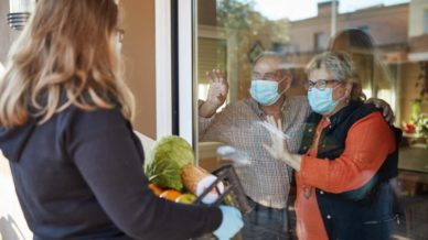 Blonde teen holds groceries in bag for older couple in mask behind glass doorVolunteer Projects Help Teens