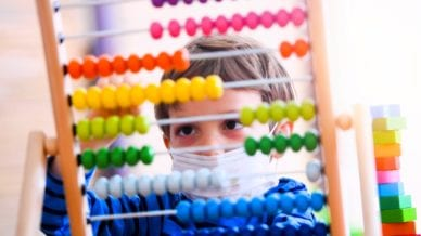 Little boy at pre school classroom wearing a protective face mask.