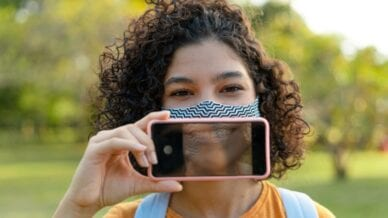 Girl smiling with mask and cell phone